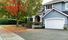 suburban home with fallen red and orange leaves on lawn from tree