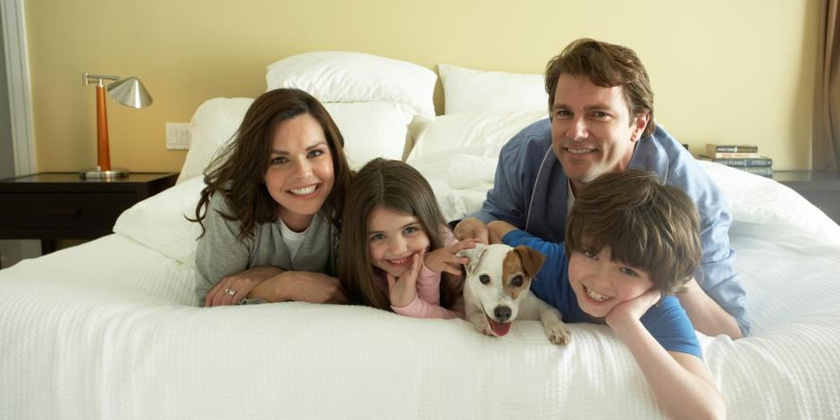 A family of four with a dog laying on a bed