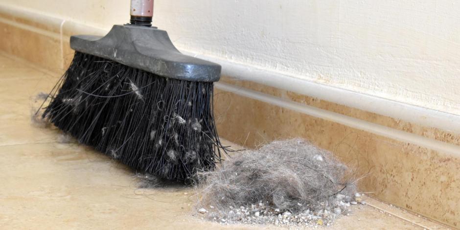 pile of dust on floor next to broom